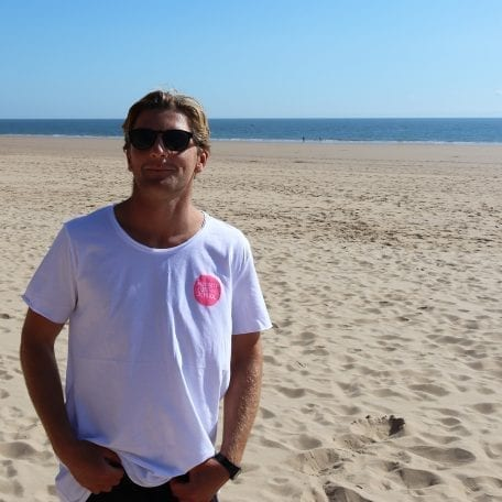 Rhys on beach in hot pink long T back print side small logo
